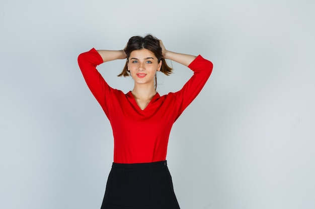 Jonge dame met haarlok in rode blouse, rok en er prachtig uit
