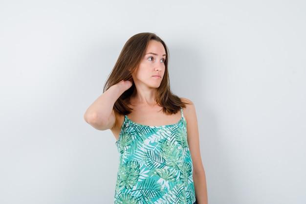 Jonge dame met hand achter hoofd in blouse en peinzend, vooraanzicht.