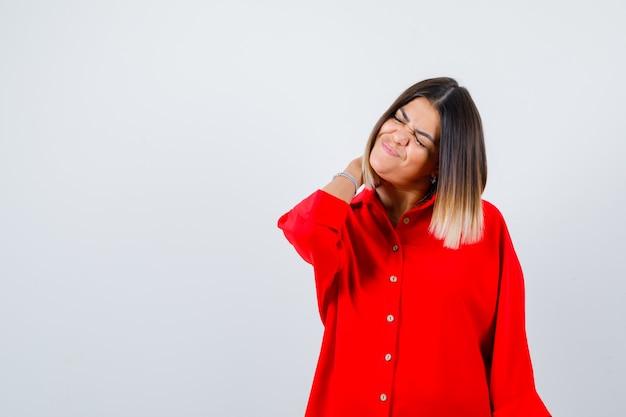 Jonge dame met hand achter nek in rood oversized shirt en pijnlijk op zoek. vooraanzicht.