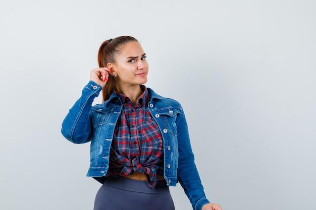 Jonge dame met hand dichtbij oor in overhemd, jasje en nieuwsgierig kijkend, vooraanzicht.