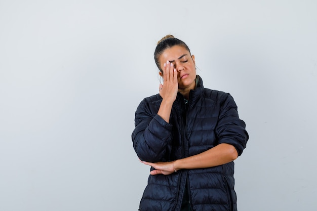 Jonge dame met hand op gezicht in pufferjack en ziet er moe uit. vooraanzicht.