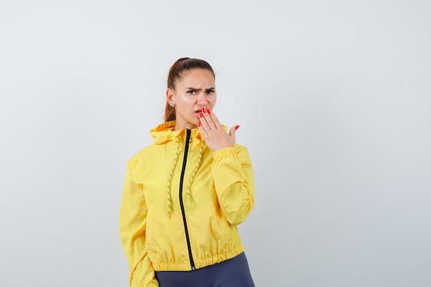Jonge dame met hand op mond in geel jasje en angstig kijkend. vooraanzicht.
