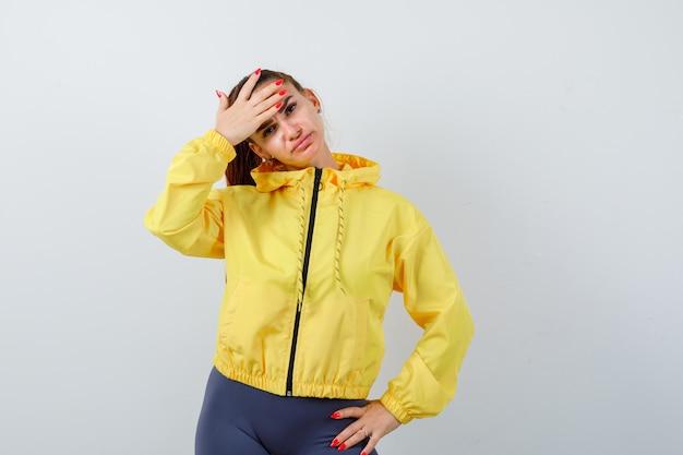 Jonge dame met hand op voorhoofd in gele jas en teleurgesteld, vooraanzicht.
