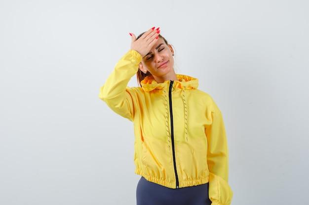 Jonge dame met hand op voorhoofd in gele jas en ziet er moe uit, vooraanzicht.