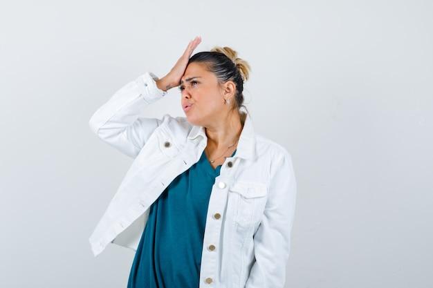 Jonge dame met hand op voorhoofd in overhemd, witte jas en vergeetachtig kijken. vooraanzicht.