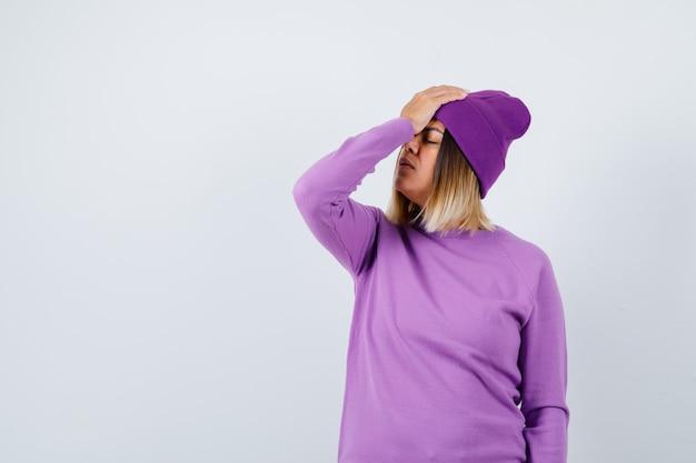 Jonge dame met hand op voorhoofd in paarse trui, muts en ziet er moe uit. vooraanzicht.