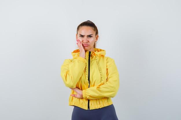 Jonge dame met hand op wang in gele jas en attent op zoek. vooraanzicht.
