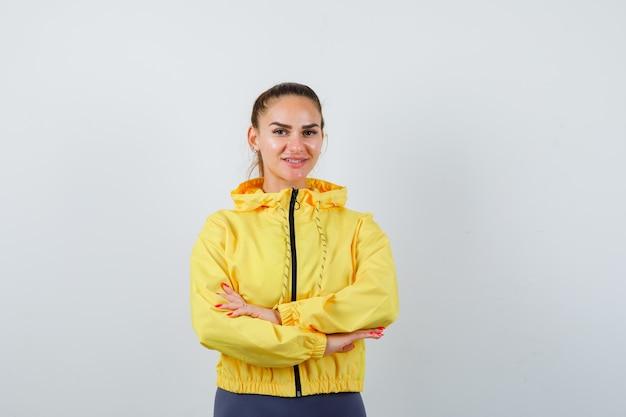 Jonge dame met handen gekruist in gele jas en vrolijk, vooraanzicht.