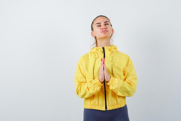 Jonge dame met handen in biddend gebaar in geel jasje en hoopvol kijkend. vooraanzicht.