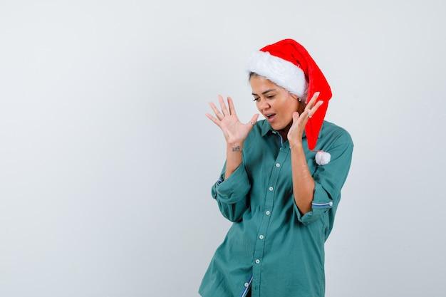 Jonge dame met handen in de buurt van gezicht in kerstmuts, shirt en verbaasd kijken. vooraanzicht.