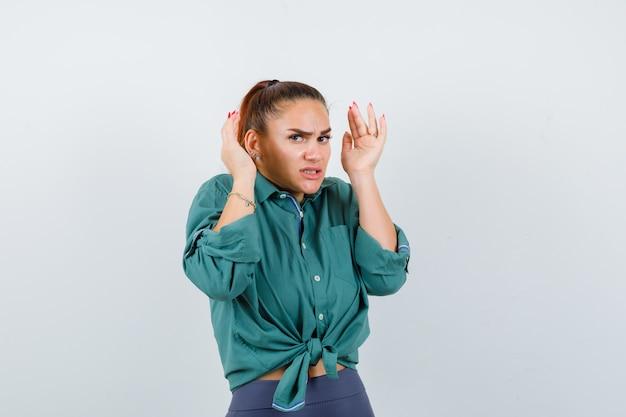 Jonge dame met handen in de buurt van hoofd in shirt, broek en angstig, vooraanzicht.