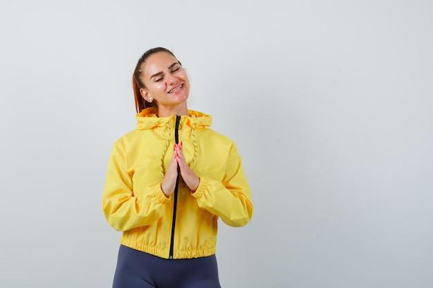 Jonge dame met handen op de borst in gele jas en er gelukkig uitzien, vooraanzicht.