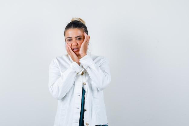 Jonge dame met handen op de wangen in shirt, witte jas en ziet er aantrekkelijk uit. vooraanzicht.