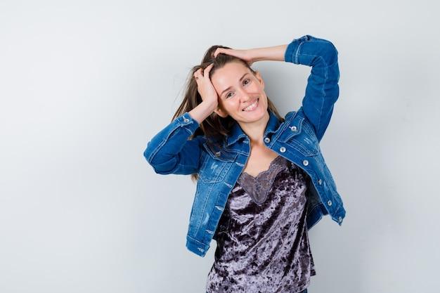 Jonge dame met handen op het hoofd in blouse, spijkerjasje en er gelukkig uitzien. vooraanzicht.