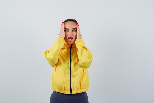 Jonge dame met handen op het hoofd, mond openend in gele jas en doodsbang kijkend. vooraanzicht.