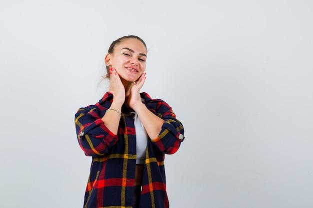 Jonge dame met handen op kin in top, geruit hemd en vrolijk, vooraanzicht.