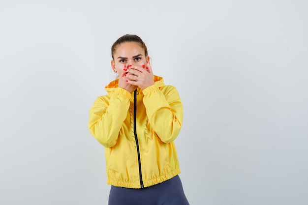 Jonge dame met handen op mond in gele jas en verbaasd kijkend, vooraanzicht.