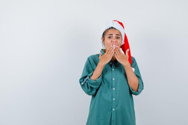 Jonge dame met handen op mond in kerstmuts, shirt en bang op zoek. vooraanzicht.