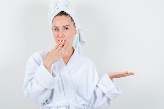 Jonge dame met handen op mond terwijl iets in witte badjas, handdoek wordt getoond en verast, vooraanzicht kijkt.