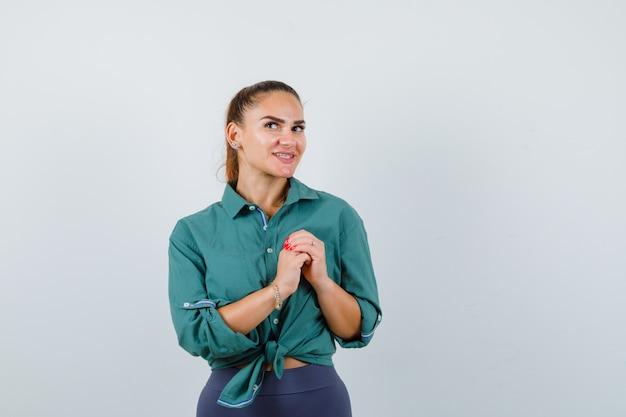 Jonge dame met handen over de borst in een groen shirt en ziet er gelukkig uit. vooraanzicht.