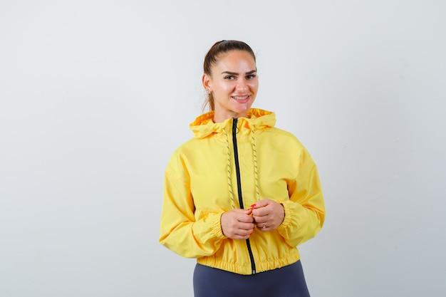 Jonge dame met handen voor haar in geel jasje en vrolijk kijkend. vooraanzicht.