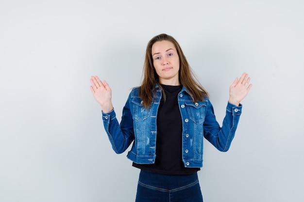 Jonge dame met handpalmen in overgavegebaar in shirt, jas en zelfverzekerd, vooraanzicht.