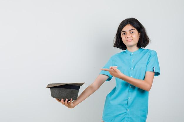 Jonge dame met hoed achteruit terwijl ze ernaar wijst in blauw shirt