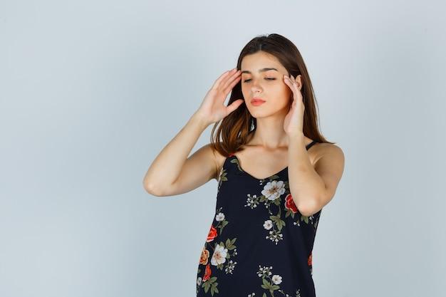 Jonge dame met hoofdpijn in blouse en uitgeput op zoek. vooraanzicht.