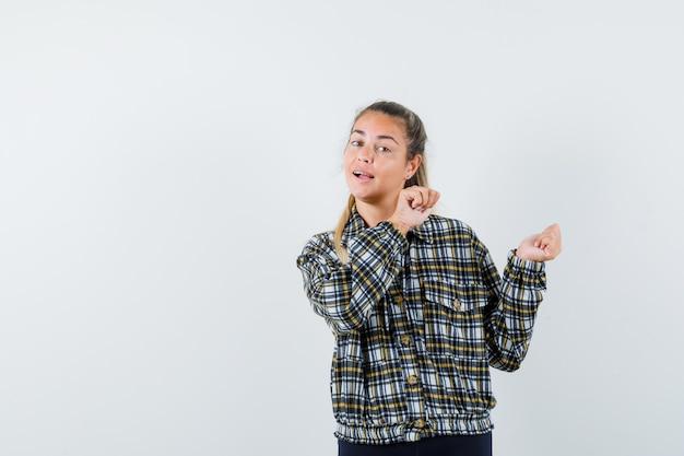 Jonge dame met iets met vuisten in shirt, korte broek en op zoek naar zelfverzekerd, vooraanzicht.