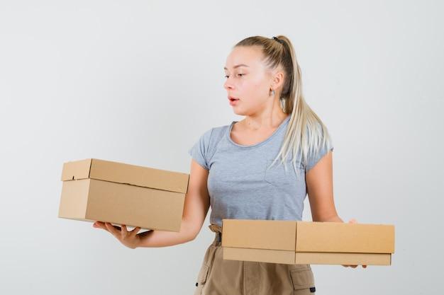 Jonge dame met kartonnen dozen in t-shirt, broek en op zoek gericht, vooraanzicht.