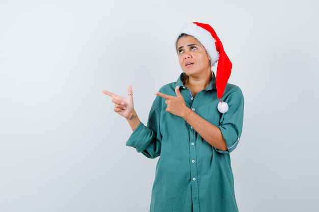 Jonge dame met kerstmuts, shirt wijzend naar de linkerkant en angstig kijkend, vooraanzicht.