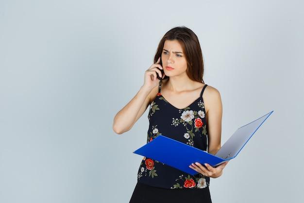Jonge dame met map, praten op mobiele telefoon in blouse en verward kijken. vooraanzicht.