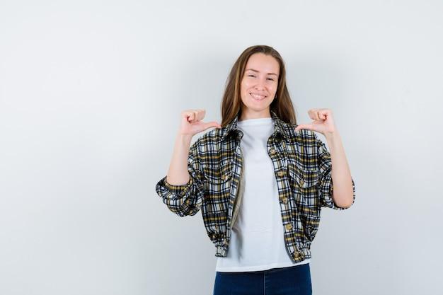 Jonge dame met middelste duimen in t-shirt, jasje, spijkerbroek en op zoek gelukkig, vooraanzicht.