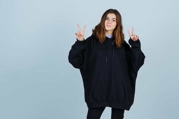 Jonge dame met overwinningsteken in oversized hoodie, broek en op zoek naar geluk, vooraanzicht.