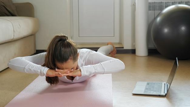 Jonge dame met paardenstaart in trainingspak doet sportoefeningen op mat en kijkt naar video op moderne laptop op de vloer in de buurt van bank in lichte kamer