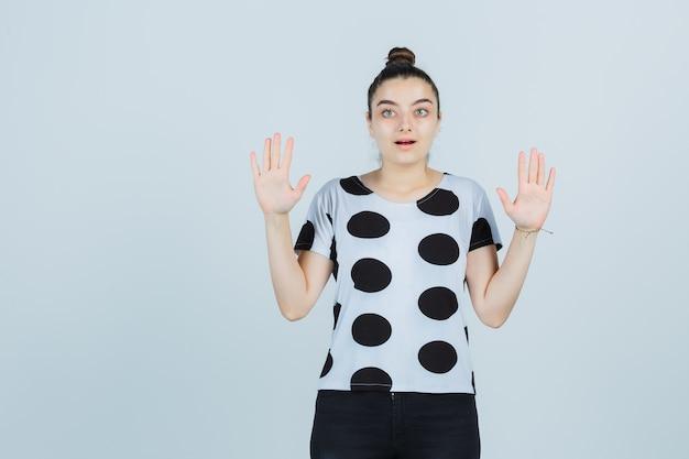 Jonge dame met palmen in overgave gebaar in t-shirt, spijkerbroek en hulpeloos op zoek. vooraanzicht.