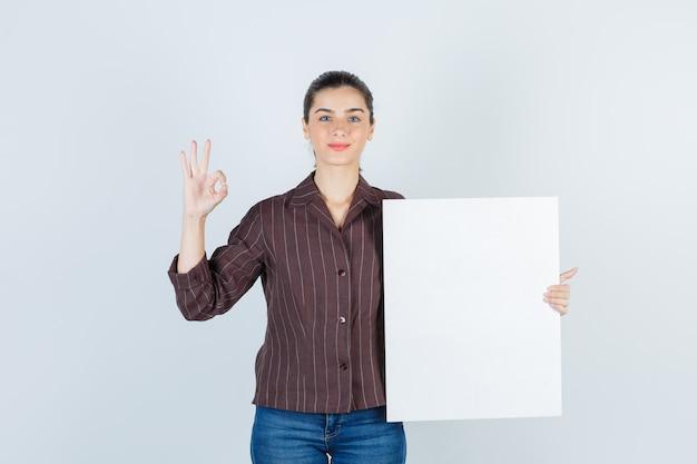 Jonge dame met papieren poster, ok gebaar in shirt, spijkerbroek en zelfverzekerd, vooraanzicht.