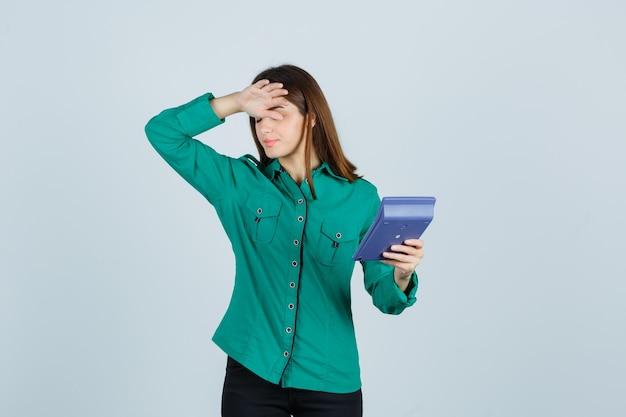 Jonge dame met rekenmachine terwijl hand op voorhoofd in groen shirt en gefrustreerd op zoek. vooraanzicht.
