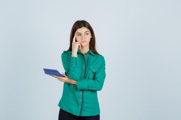 Jonge dame met rekenmachine terwijl vinger op tempels in groen shirt en peinzend, vooraanzicht op zoek.