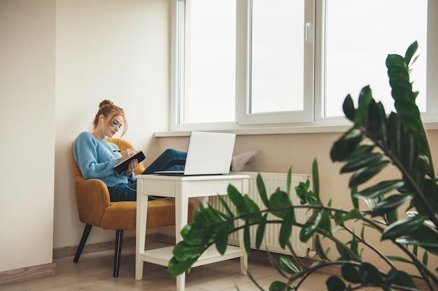 Jonge dame met rood haar en sproeten die hydrogel-oogpaden dragen terwijl ze in het boek iets schrijft met een laptop in de buurt