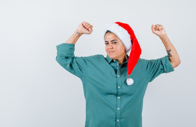 Jonge dame met spieren van armen in kerstmuts, shirt en zelfverzekerd, vooraanzicht.