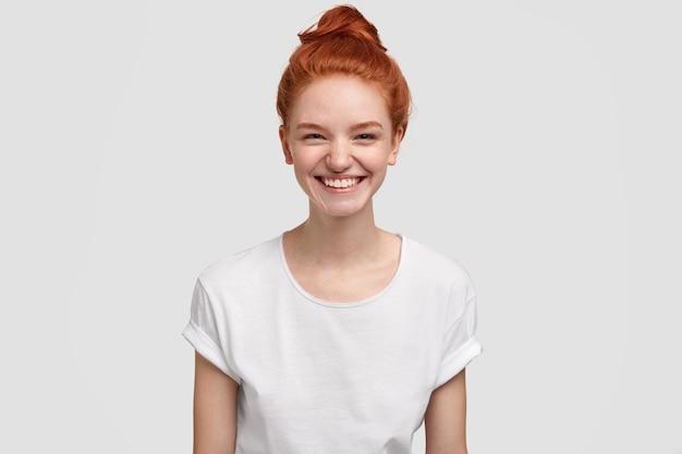 Jonge dame met sproeten of tiener glimlacht vreugdevol naar de camera