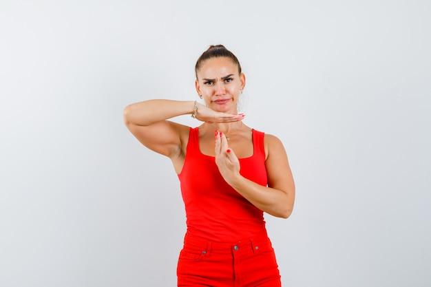 Jonge dame met time-out in rood hemd, rode broek en zelfverzekerd op zoek. vooraanzicht.