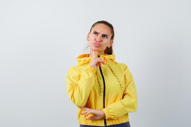 Jonge dame met vinger op kin in gele jas en attent. vooraanzicht.