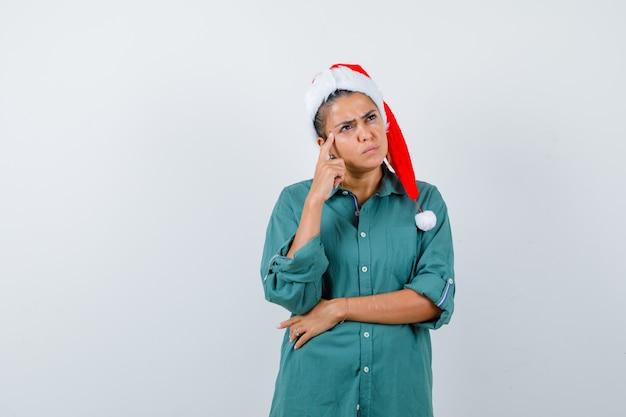 Jonge dame met vinger op tempels in kerstmuts, shirt en peinzend kijkend. vooraanzicht.