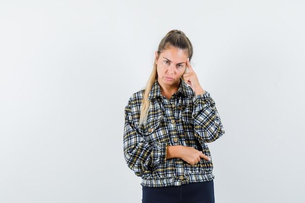 Jonge dame met vinger op tempels in shirt, korte broek en op zoek naar serieuze, vooraanzicht.