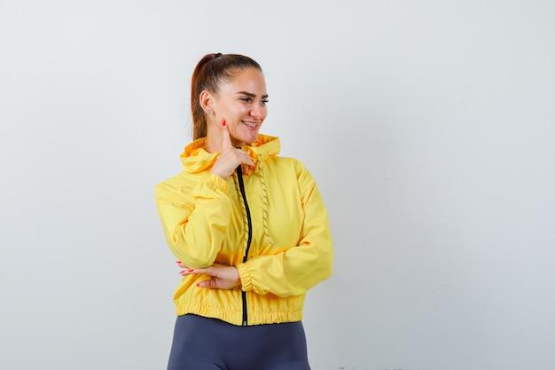 Jonge dame met vinger op wang in gele jas en vrolijk, vooraanzicht.