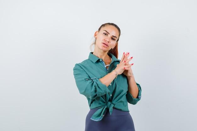 Jonge dame met vingers geklemd in groen shirt en peinzend, vooraanzicht.