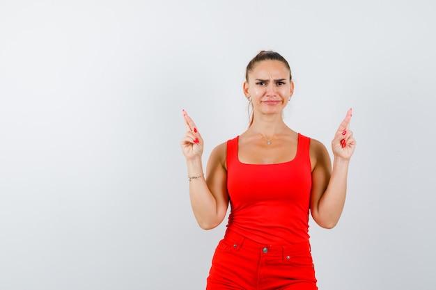 Jonge dame met vingers gekruist in rood hemd, rode broek en serieus op zoek, vooraanzicht.