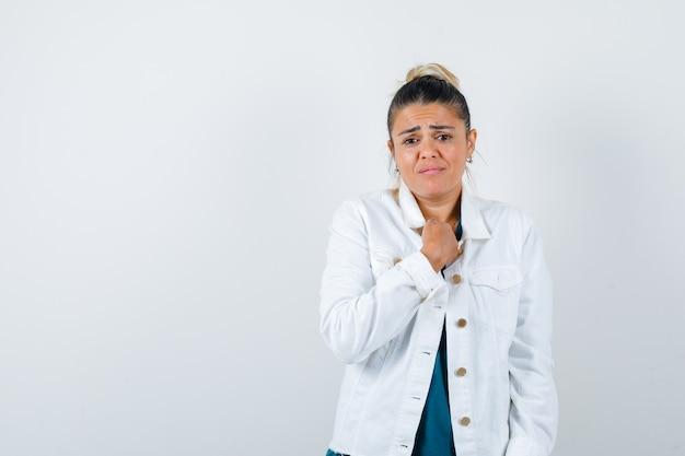 Jonge dame met vuist op borst in shirt, witte jas en verdrietig, vooraanzicht.